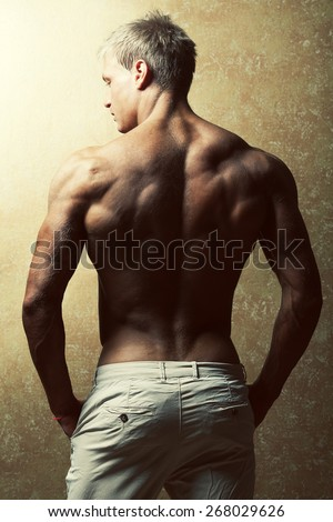 Male beauty & fashion concept. Portrait of handsome muscular male model in trendy summer pants posing over golden background. Blond hair and healthy clean skin. Studio shot - stock photo