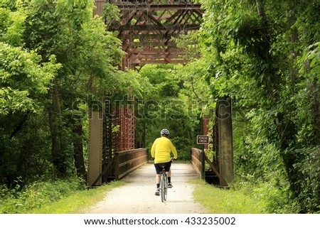 Male bicyclist approaching an old railroad bridge; Midwest; horizontal