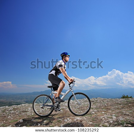 Male bicyclist riding a bike on a mountain - stock photo