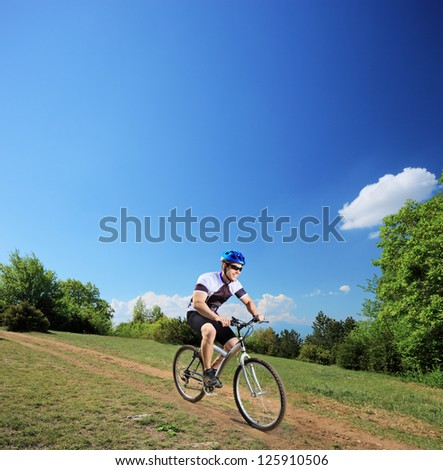 Male bicyclist riding a mountain bike downhill, shot with a tilt and shift lens - stock photo