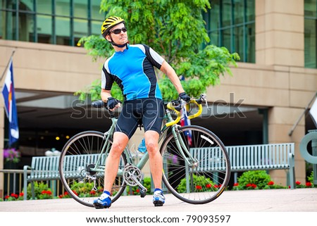 Male bike rider resting in downtown - stock photo