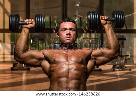 male bodybuilder doing shoulder press whit dumbbell - stock photo