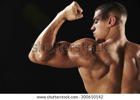Male bodybuilder flexing bicep, back view with copy space - stock photo