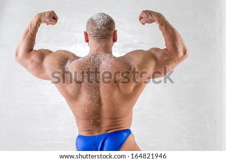 Male bodybuilder in trunks with snow on body posing back in studio - stock photo