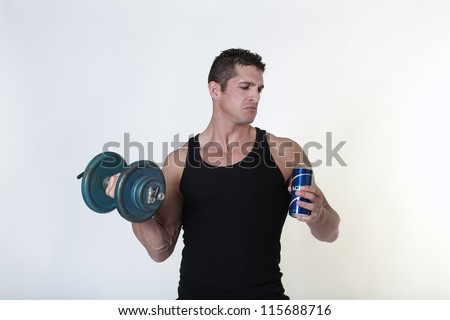 male bodybuilder not sure if he should have a drink of beer or carry on with his work out - stock photo