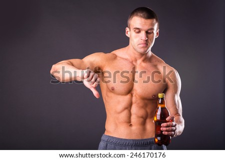 Male bodybuilder shows that beer is bad. Unhealthy eating habits. If you want to be healthy and strong do not drink beer. - stock photo