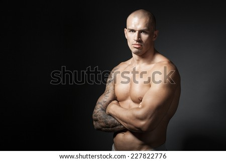 male bodybuilder with folded arms isolated on gray background with copyspace