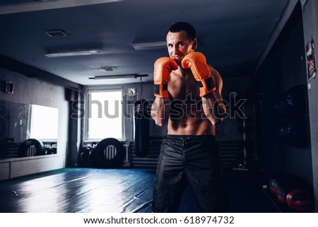 Male boxer training with punching bag in dark gym. Young boxer training on punching bag. Male boxer as exercise for the big fight. Young masculine male athlete. Portrait of brutal fighter