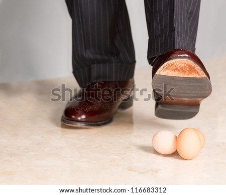 Male brown leather shoe in suit pants about to tread on three brown eggs - stock photo