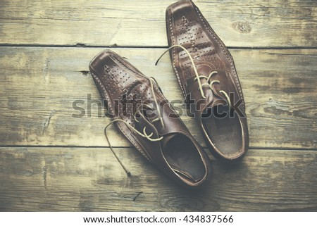 male brown shoes over the wooden table