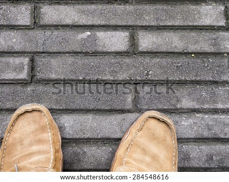 Male, brown suede shoes on concrete tiles