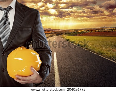 Male builder with helmet standing on highway to new achievement. Right career path and mission concept. - stock photo