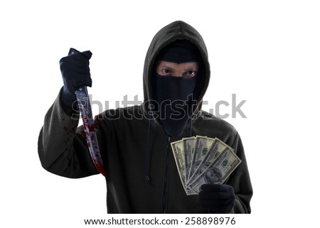 Male burglar wearing mask and hoodie while holding a bloody knife and money cash, isolated on white - stock photo