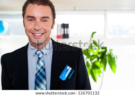 Male business executive in formals with cash card popping out of his blazer pocket.
