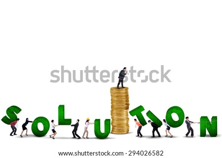 Male business leader standing on a pile of golden coins while giving a command on his team to create a solution - stock photo