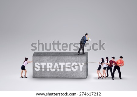 Male business leader standing on a stone and command his team to remove the stone with a strategy - stock photo