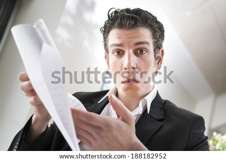 Male business man trying to communicate information about his papers. This deal is not feasible or sustainable. Could he be angry or worried. Mediterranean and asian facial features. - stock photo
