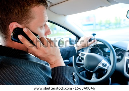 male businessman talking on a cell phone while driving - stock photo