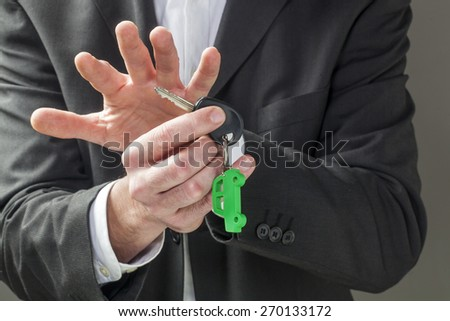 male businessman with green car key holder in his hands - stock photo