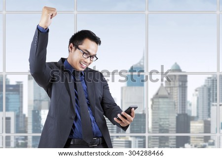 Male businessperson in business suit expressing success while reading a message near the window - stock photo