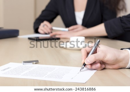 Male businessperson signs contract. Close up of female hand signing formal paper on the office table. The business counterpart on the background