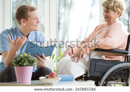 Male care assistant reading senior woman book - stock photo