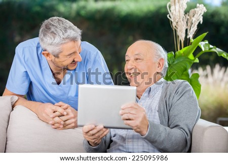 Male caretaker and senior man laughing while using tablet computer at nursing home porch - stock photo
