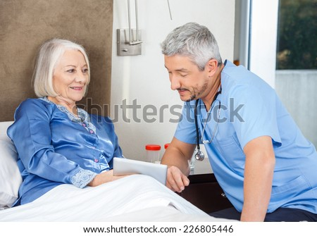 Male caretaker and senior woman using tablet PC in bedroom at nursing home - stock photo