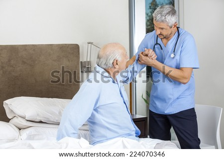 Male caretaker assisting senior man to get up from bed at nursing home - stock photo