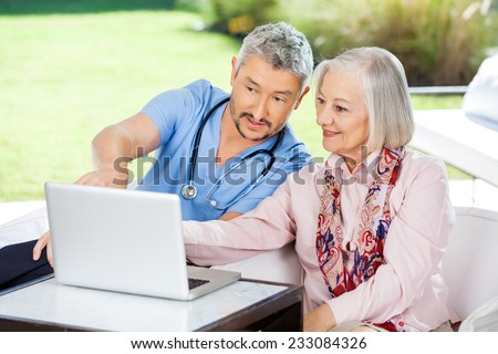 Male caretaker assisting senior woman in using laptop at nursing home porch - stock photo