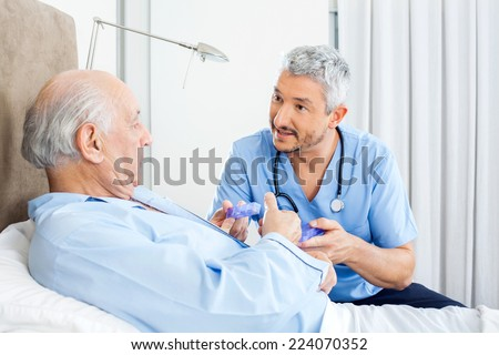 Male caretaker explaining prescription to senior man in bedroom at nursing home - stock photo