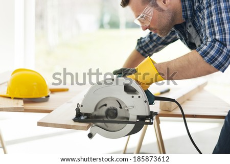 Male carpenter sawing wooden boards   - stock photo