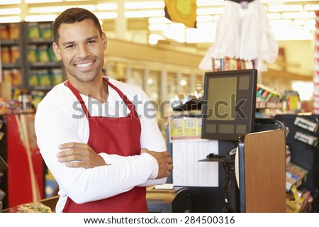 Male Cashier At Supermarket Checkout - stock photo
