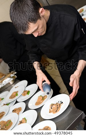 male caucasian chef in black uniform pour sauce on plates with lamb meat - stock photo
