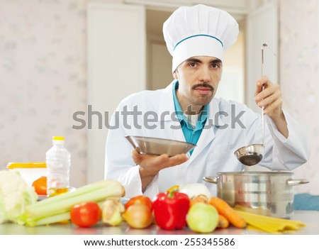 Male caucasian cook cooking with ladle - stock photo