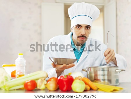 Male caucasian cook cooking with ladle in kitchen - stock photo