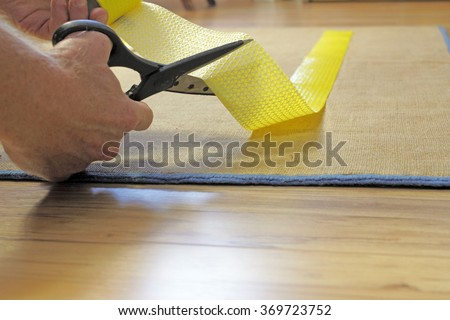 Male caucasian hands with black handle stainless steel scissors cutting to size a strip of yellow anti-slip rug grip tape. Cutting and placing anti-skid carpet tape.