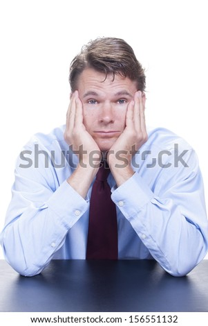 Male Caucasian office worker sits at desk with elbows on table and face sunk into his hands as he stares into camera with heavy boredom on white background - stock photo