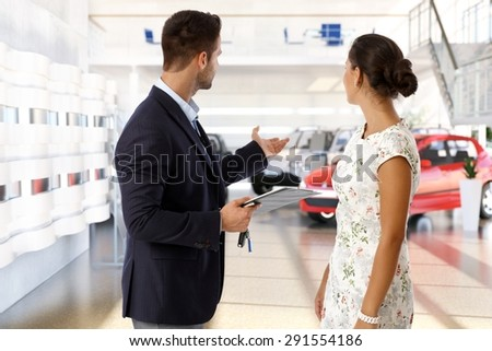 Male caucasian salesman and female client at the car dealership saloon indoors. Standing, wearing suit, looking away, gesturing, pointing, presenting with business checklist and keys in hand.