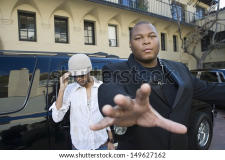Male celebrity with his bodyguard against a vehicle - stock photo