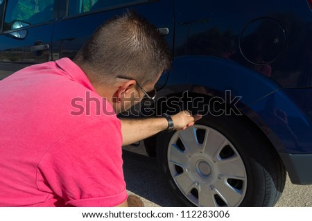 Male checking the general state of his tyres - stock photo