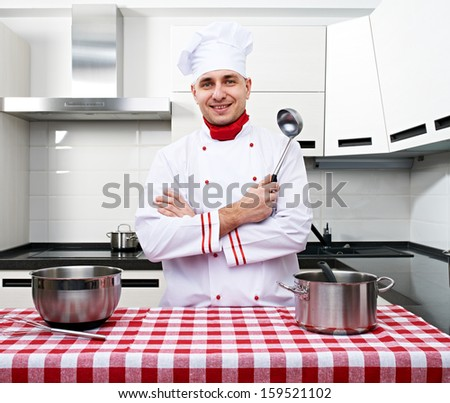 Male chef at kitchen getting ready to cook - stock photo