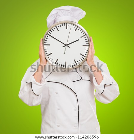 Male Chef Holding A Clock In Front Of Face On Green Background