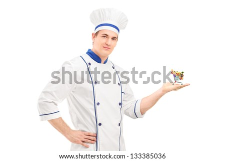 Male chef holding a small shopping cart with food products, isolated on white background - stock photo