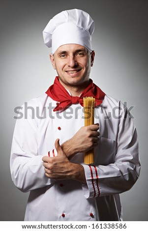 Male chef holding pasta against grey background - stock photo