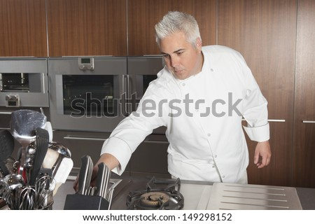 Male chef leaning for knife in commercial kitchen - stock photo