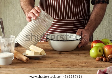 Male chef prepares a pie with apples. Man pours flour into a bowl for making the dough for the pie - stock photo