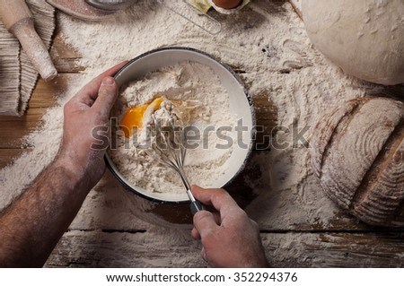 Male chef prepares. Man mixes whisk eggs. Top view - stock photo