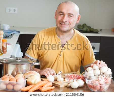 male chef preparing  dish of meat - stock photo