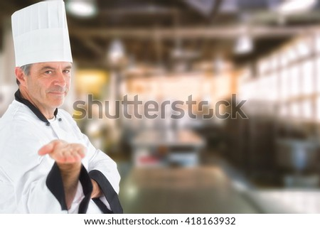 Male chef presenting an invisible product against no one in the room - stock photo